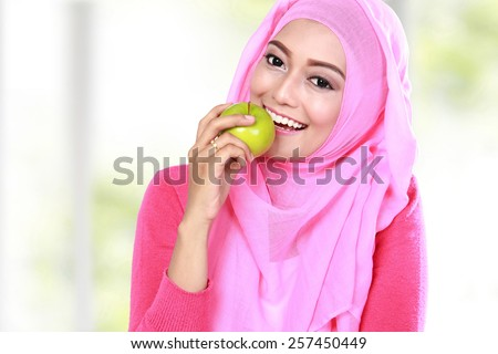 portrait of beautiful young muslim woman bite an apple - stock photo