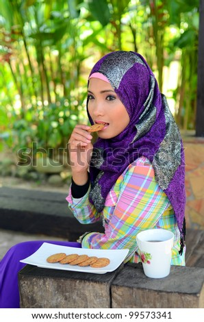 Portrait of beautiful young muslim woman having breakfast at the park