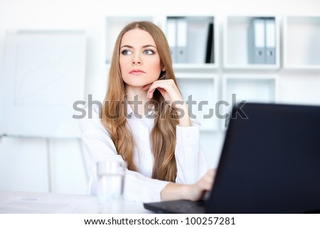 Portrait of beautiful young pensive business woman working on a laptop at office - stock photo