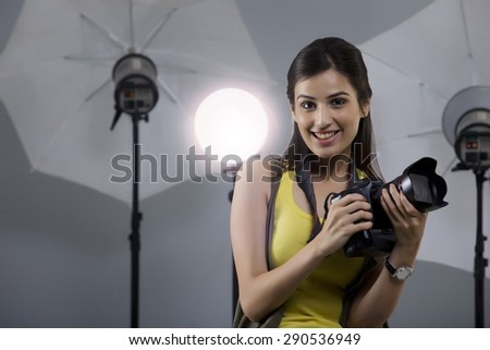 Portrait of beautiful young photographer holding camera in her studio - stock photo
