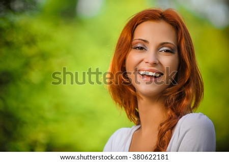 Portrait of beautiful young redhead woman wearing white blouse at summer green park. - stock photo