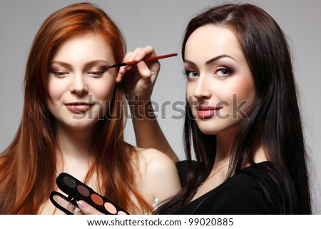 Portrait of beautiful young redheaded woman with esthetician making makeup eye shadow - stock photo