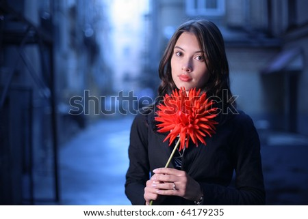 Portrait of beautiful young romantic woman with red flower outdoor in twilight blue city.Closeup, shallow DOF.