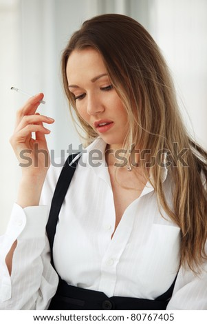 Portrait of beautiful young sad blond woman with a cigarette - stock photo
