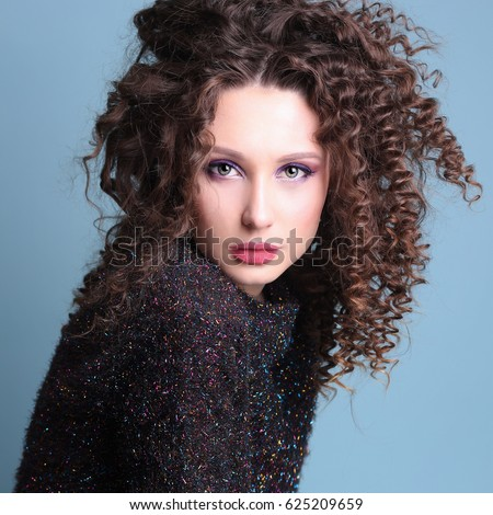 Portrait of beautiful young sexy lady with curly disheveled hair style. Fashion studio photo