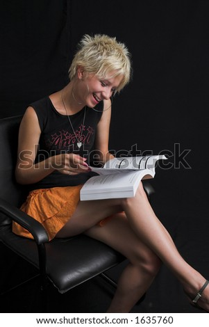Portrait of beautiful young sexy woman on black background - holding a book