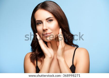 portrait of beautiful young smiling brunette woman, on bright blue background - stock photo