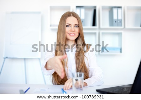 Portrait of beautiful young smiling business woman sitting at desk offering a handshake in bright office - stock photo