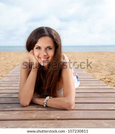Portrait of beautiful young smiling woman in colorful dress resting at beach in summer - stock photo