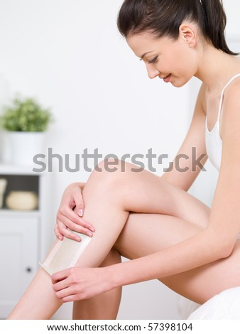 Portrait of beautiful young smiling woman in profile depilating her legs by waxing - indoors - stock photo