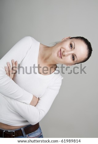 Portrait of beautiful young smiling woman, isolated on gray background - stock photo