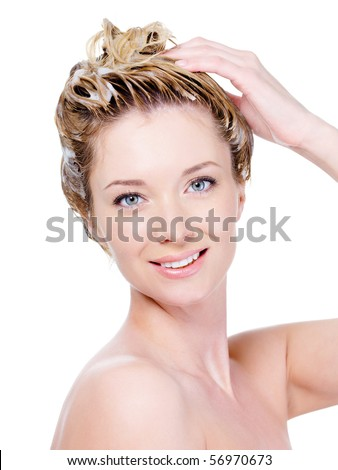 Portrait of beautiful young smiling woman washing her hair - isolated on white - stock photo