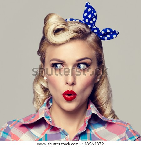 Portrait of beautiful young surprised woman, dressed in pin-up style. Caucasian blond model posing in retro fashion and vintage concept studio shoot.