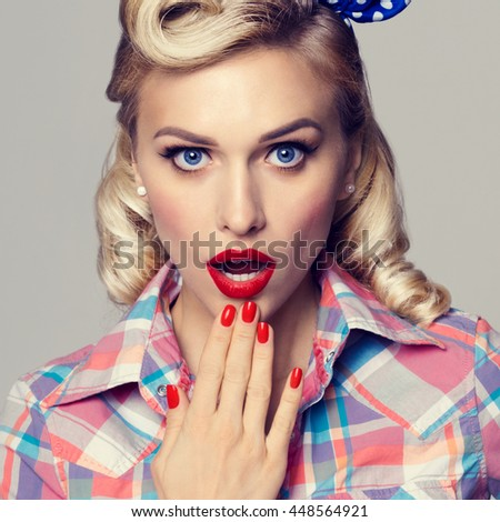 Portrait of beautiful young surprised woman, dressed in pin-up style. Caucasian blond model posing in retro fashion and vintage concept studio shoot. - stock photo