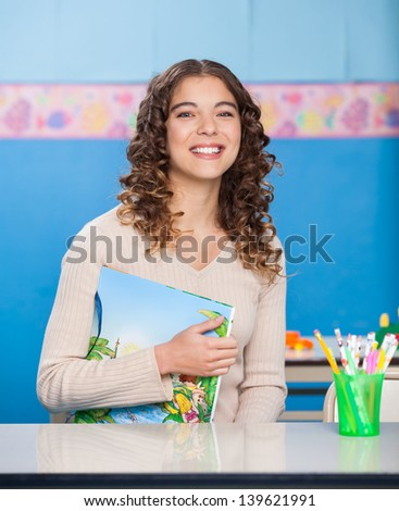 Portrait of beautiful young teacher with book sitting at desk in preschool - stock photo