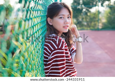 portrait of beautiful young teen woman leaning steel net fence and looking to camera - stock photo