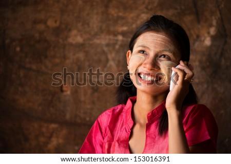 Portrait of beautiful young traditional Myanmar girl using smart phone. - stock photo