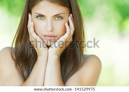 Portrait of beautiful young woman, against background of summer green park. - stock photo