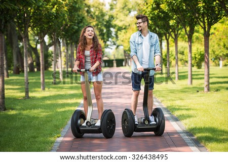 Portrait of beautiful young woman and handsome man. Girl and boy using segway. Girl cheerfully smiling. Green alley as background - stock photo
