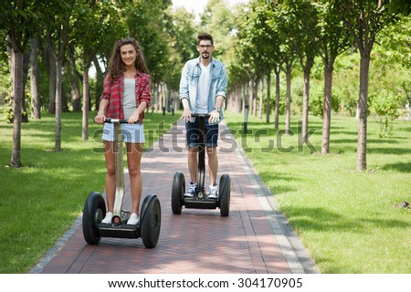 Portrait of beautiful young woman and handsome man. Girl and boy using segway. Green alley as background - stock photo