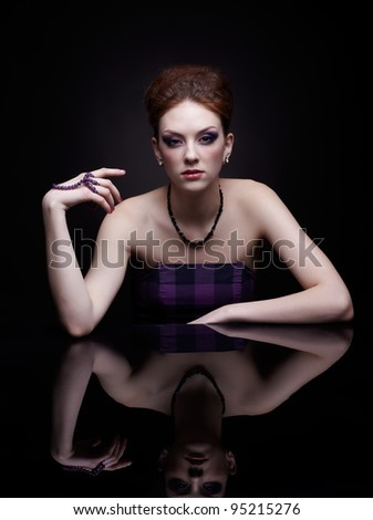 portrait of beautiful young woman at dark mirror table - stock photo