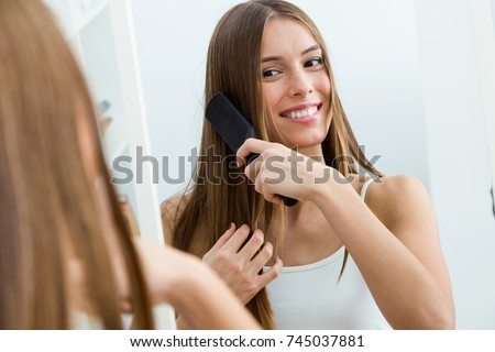 Portrait of beautiful young woman brushing her long hair in front of her mirror.