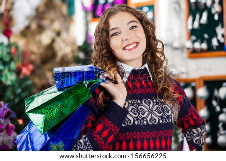 Portrait of beautiful young woman carrying shopping bags in Christmas store - stock photo