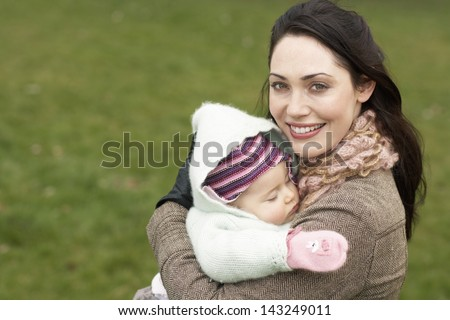Portrait of beautiful young woman carrying sleeping baby in park - stock photo