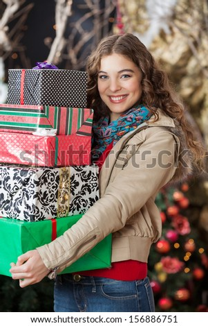 Portrait of beautiful young woman carrying stacked gift boxes in Christmas store