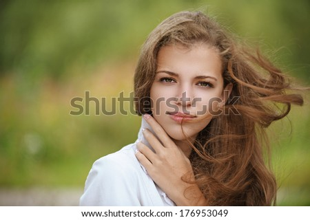 Portrait of beautiful young woman close up with wind, against background of autumn park.