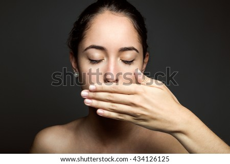 Portrait of beautiful young woman covering her mouth with hand. Isolated. - stock photo