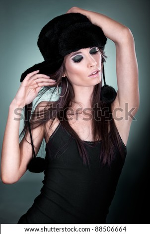 Portrait of beautiful young woman dancing on dark background - stock photo