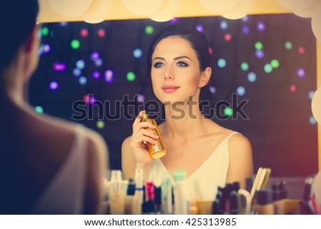 portrait of beautiful young woman doing makeup