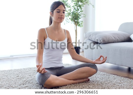 Portrait of beautiful young woman doing yoga exercises at home. - stock photo