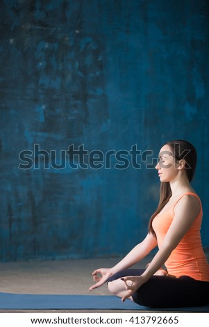 Portrait of beautiful young woman dressed in bright sportswear enjoying yoga indoors. Yogi girl working out in grunge interior with blue wall. Sitting in Half Lotus Posture. Copy space - stock photo