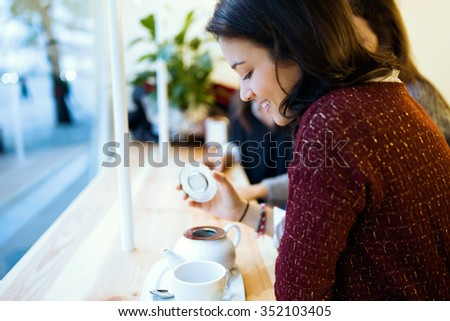 Portrait of beautiful young woman drinking coffee at cafe shop. - stock photo