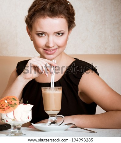 Portrait of beautiful young woman drinking coffee in restaurant