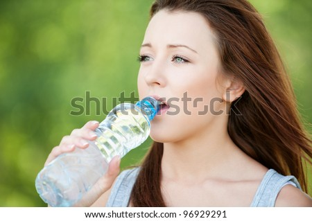 Portrait of beautiful young woman drinking water bottle at summer green park - stock photo