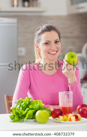 Portrait of beautiful young woman eating an apple and other fresh organic fruit and vegetable on her kitchen table