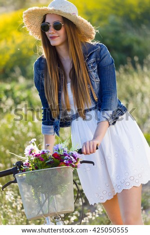 Portrait of beautiful young woman enjoying spring in a field.