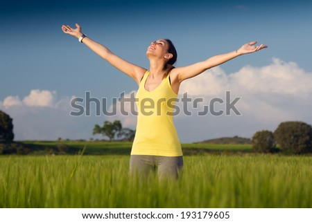 Portrait of beautiful young woman enjoying the spring standing in a cereal field - stock photo