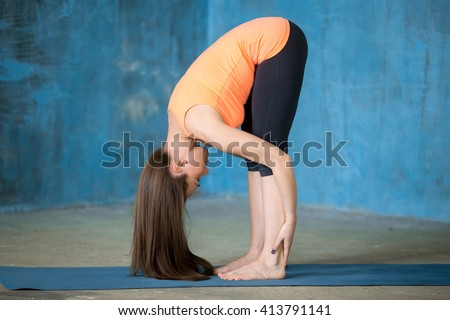 Portrait of beautiful young woman enjoying yoga indoors. Yogi girl working out in grunge interior with blue wall. Uttanasana (Intense Stretch, Standing Forward Bend pose). Full length - stock photo