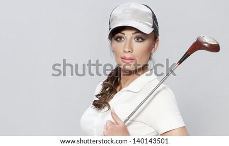Portrait of beautiful young woman, female golf player over the gray background. - stock photo