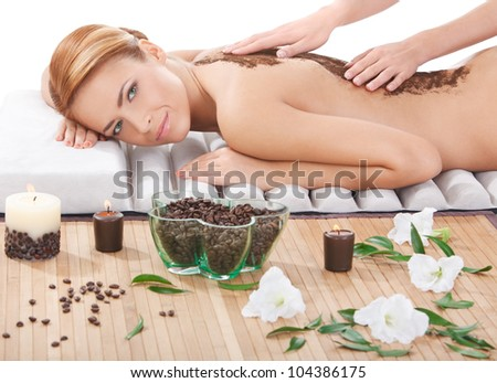 portrait of beautiful young woman getting back massage with coffee scrub at spa