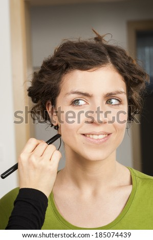 Portrait of beautiful young woman getting her make up done - stock photo