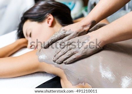 Portrait of beautiful young woman having clay body mask apply by beautician. Detox ritual.