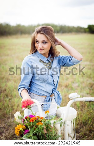 Portrait of beautiful young woman having fun with bicycle on green summer outdoors copy space background - stock photo