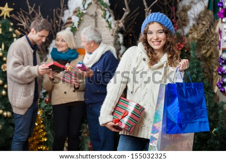 Portrait of beautiful young woman holding Christmas presents and shopping bags with family standing in background at store - stock photo