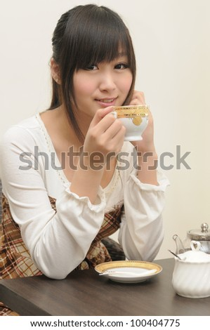Portrait of beautiful young woman holding coffee cup - stock photo
