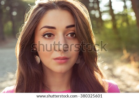 portrait of beautiful young woman in against the sun background